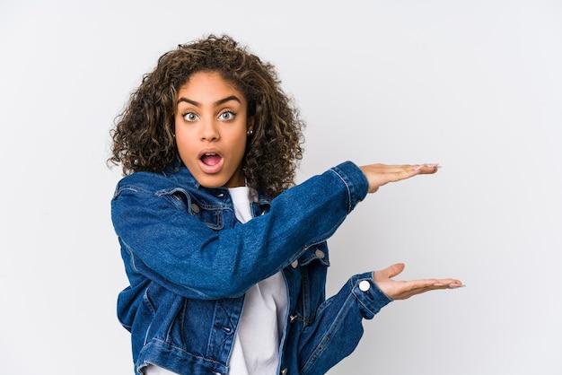 Młoda afroamerykanka zszokowana i zdumiona trzyma kopię przestrzeni między rękami.