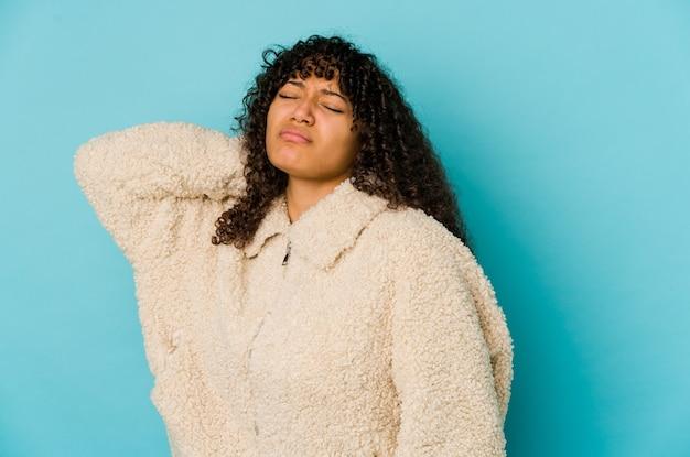 Młoda afroamerykańska afro kobieta na białym tle o bólu szyi z powodu stresu, masowania i dotykania ręką.