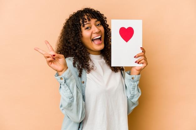Młoda afroamerykańska afro kobieta trzyma kartkę walentynkową radosny i beztroski pokazując palcami symbol pokoju.