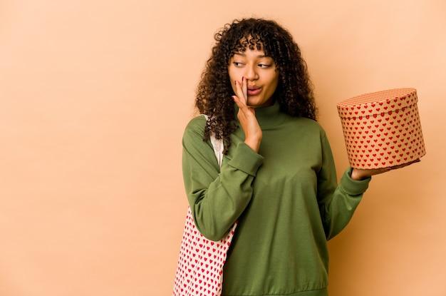 Młoda afroamerykańska afro kobieta trzyma prezent walentynkowy mówi tajną gorącą wiadomość o hamowaniu i patrzy na bok