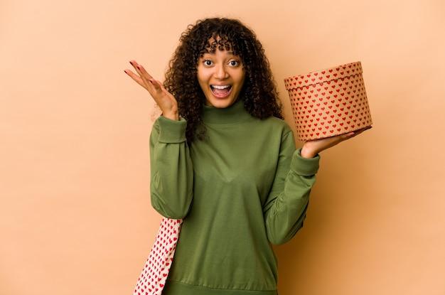 Młoda afroamerykańska afro kobieta trzyma prezent walentynkowy otrzymując miłą niespodziankę, podekscytowany i podnoszący ręce
