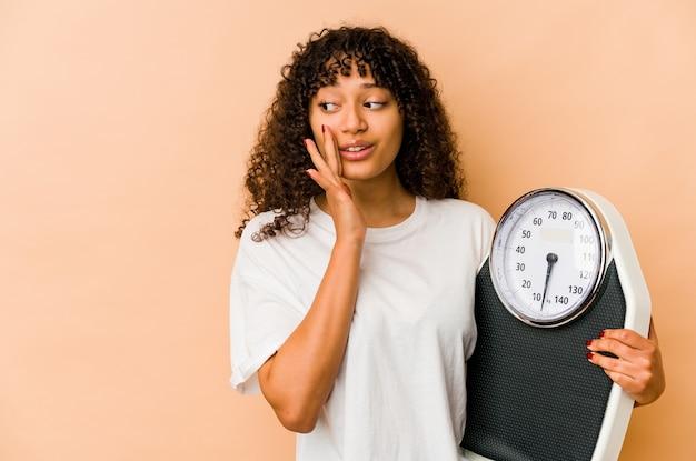 Młoda afroamerykańska afro kobieta trzymająca wagę mówi tajną gorącą wiadomość o hamowaniu i patrzy na bok