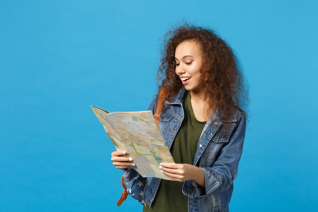 Młoda afroamerykańska dziewczyna nastoletnia studentka w dżinsowych ubraniach, mapa trzymania plecaka odizolowana na niebieskiej ścianie