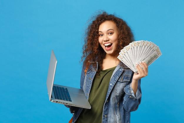 Młoda afroamerykańska dziewczyna nastoletnia studentka w dżinsowych ubraniach, plecak do trzymania komputera, fan gotówki na białym tle na niebieskiej ścianie