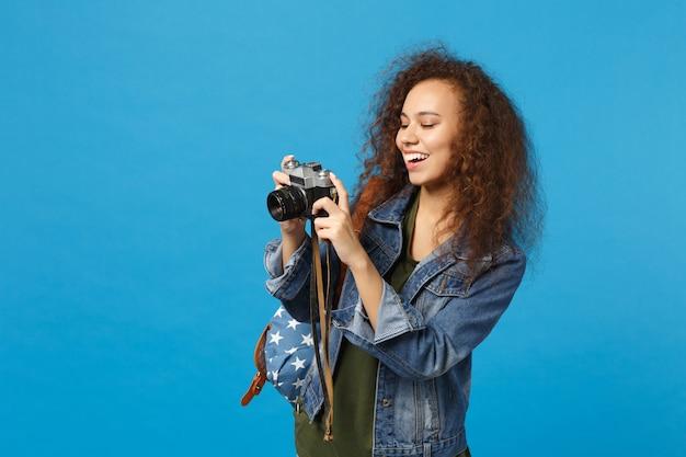 Młoda afroamerykańska dziewczyna nastoletnia studentka w dżinsowych ubraniach plecak trzyma aparat odizolowany na niebieskiej ścianie blue