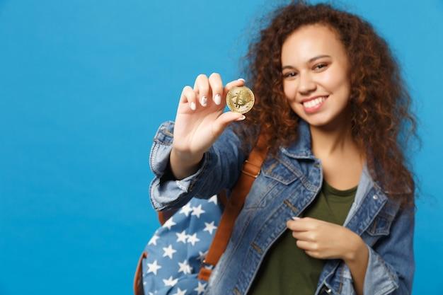 Młoda afroamerykańska dziewczyna nastoletnia studentka w dżinsowych ubraniach, plecak trzyma bitcoina na białym tle na niebieskiej ścianie
