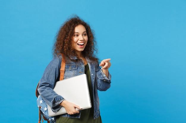 Młoda afroamerykańska dziewczyna nastoletnia studentka w dżinsowych ubraniach, plecak trzyma komputer na białym tle na niebieskiej ścianie