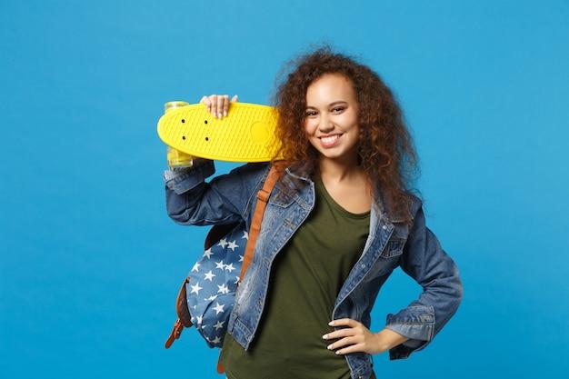 Młoda afroamerykańska dziewczyna nastoletnia studentka w dżinsowych ubraniach, plecak trzyma łyżwę na białym tle na niebieskiej ścianie
