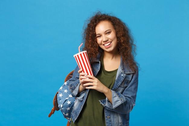 Młoda afroamerykańska dziewczyna nastoletnia studentka w dżinsowych ubraniach, plecak trzyma papierowy kubek na białym tle na niebieskiej ścianie