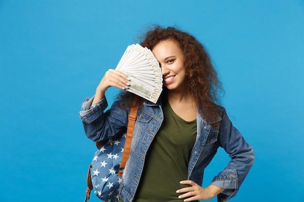 Młoda afroamerykańska dziewczyna nastoletnia studentka w dżinsowych ubraniach, plecak trzyma pieniądze na białym tle na niebieskiej ścianie