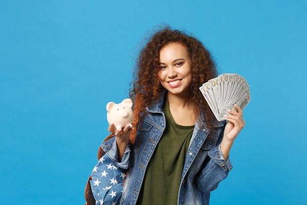 Młoda afroamerykańska dziewczyna nastoletnia studentka w dżinsowych ubraniach, plecak trzyma świnię odizolowaną na niebieskiej ścianie