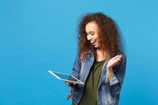 Młoda afroamerykańska dziewczyna nastoletnia studentka w dżinsowych ubraniach, plecak trzymaj pad pc odizolowany na niebieskiej ścianie