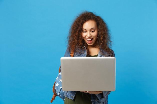 Młoda afroamerykańska dziewczyna nastoletnia studentka w dżinsowych ubraniach, praca z plecakiem na komputerze na białym tle na niebieskiej ścianie
