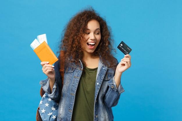 Młoda afroamerykańska dziewczyna nastoletnia studentka w dżinsowych ubraniach, przepustka do plecaka odizolowana na niebieskiej ścianie