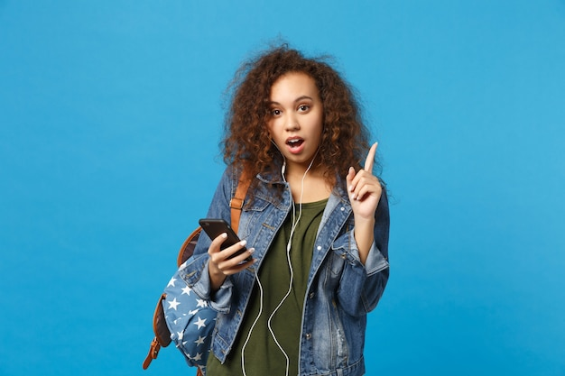Młoda afroamerykańska dziewczyna nastoletnia studentka w dżinsowych ubraniach, słuchawki plecakowe izolowane na niebieskiej ścianie