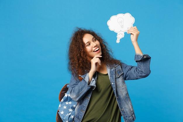 Młoda afroamerykańska dziewczyna nastoletnia studentka w dżinsowych ubraniach, zegar trzymający plecak na białym tle na niebieskiej ścianie