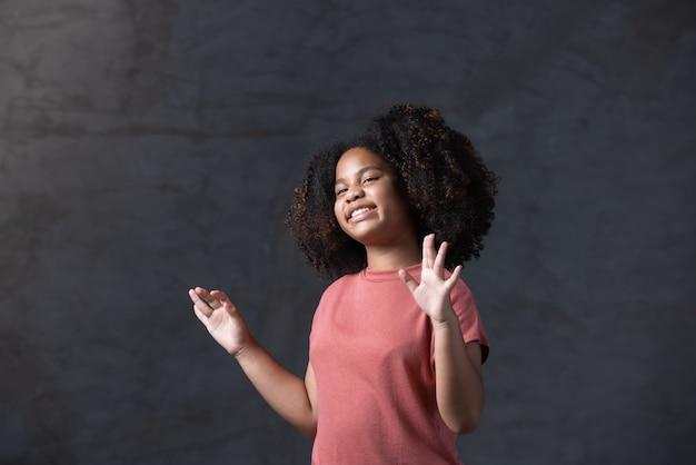 Młoda afroamerykańska dziewczyna z kręconymi włosami tańczy