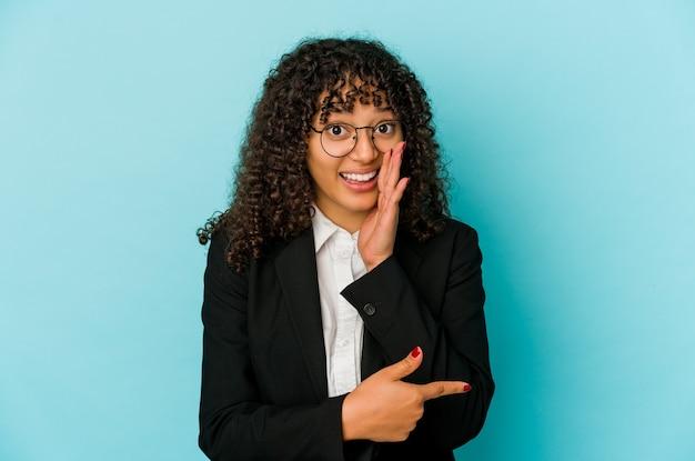Młoda afroamerykańska kobieta afro na białym tle mówiąc plotki, wskazując na bok, zgłaszając coś.
