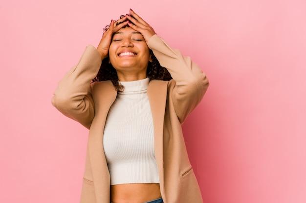 Młoda afroamerykańska kobieta afro na białym tle śmieje się radośnie trzymając ręce na głowie. koncepcja szczęścia.