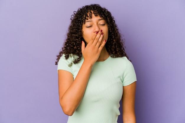 Młoda afroamerykańska kobieta afro na białym tle ziewanie pokazując zmęczony gest obejmujący usta ręką.