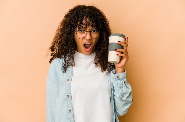Młoda afroamerykańska kobieta afro trzyma kawę na wynos krzycząc bardzo zły i agresywny.