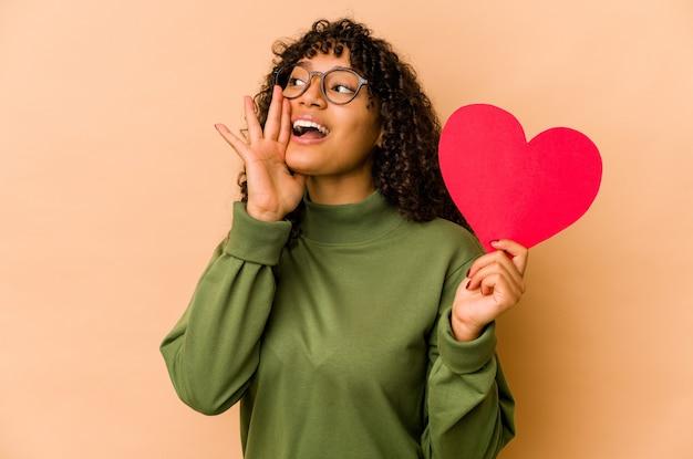 Młoda afroamerykańska kobieta afro trzyma serce walentynki, krzycząc i trzymając dłoń w pobliżu otwartych ust.