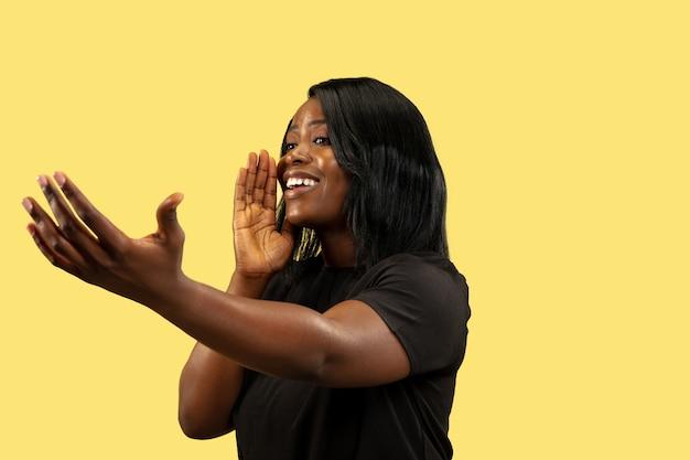 Młoda afroamerykańska kobieta na białym tle na żółtej przestrzeni, wyraz twarzy. piękny portret kobiety w połowie długości.