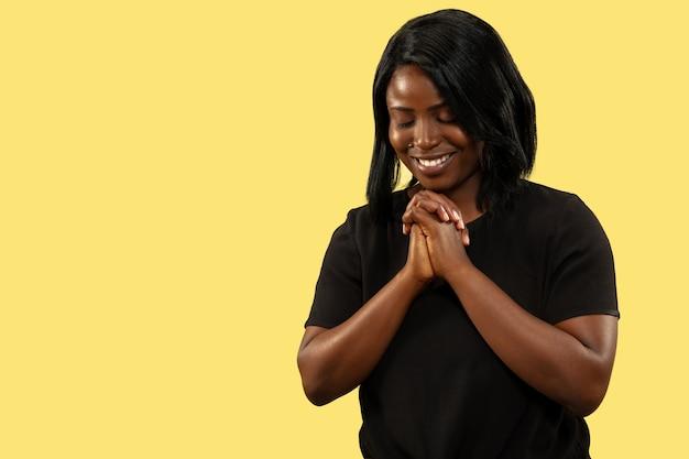 Młoda afroamerykańska kobieta na białym tle na żółtym tle studio, wyraz twarzy. piękny portret kobiety w połowie długości. pojęcie ludzkich emocji, wyraz twarzy. modląc się i uśmiechając.