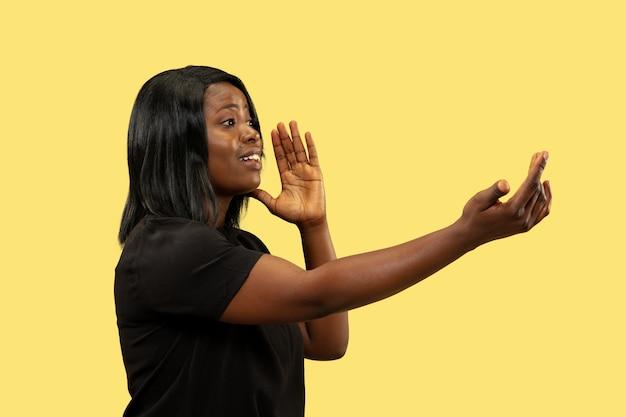 Młoda afroamerykańska kobieta na białym tle na żółtym tle studio, wyraz twarzy. piękny portret kobiety w połowie długości. pojęcie ludzkich emocji, wyraz twarzy. wołanie kogoś.