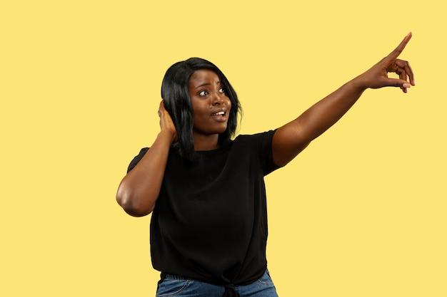 Młoda afroamerykańska kobieta na białym tle na żółtym tle studio, wyraz twarzy. piękny portret kobiety w połowie długości. pojęcie ludzkich emocji, wyraz twarzy. wybieranie i wskazywanie w górę.