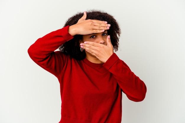 Młoda afroamerykańska kobieta rasy mieszanej na białym tle mrugając do kamery przez palce, zawstydzona zakrywająca twarz.