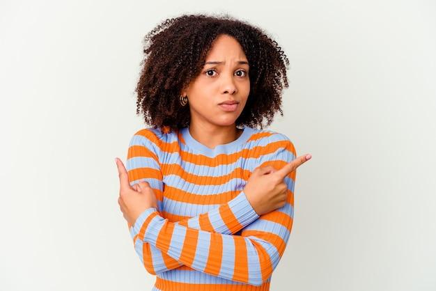 Młoda afroamerykańska kobieta rasy mieszanej odizolowane na boki, próbuje wybrać jedną z dwóch opcji.