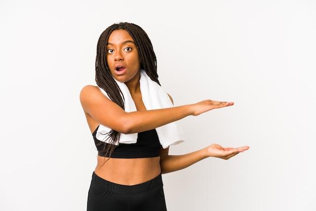 Młoda afroamerykańska kobieta sport odizolowana zszokowana i zdumiona trzyma kopię przestrzeni między rękami.