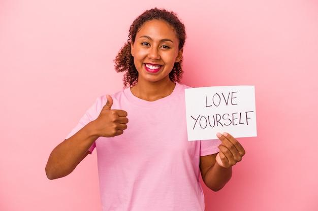 Młoda afroamerykańska kobieta trzyma kochaj siebie afisz na białym tle na różowym tle