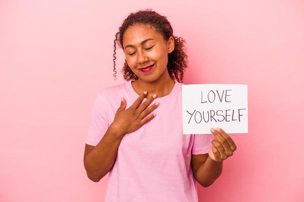Młoda afroamerykańska kobieta trzyma miłość siebie afisz na białym tle na różowym tle