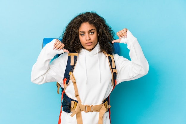 Młoda afroamerykańska kobieta z plecakiem czuje się dumna i pewna siebie, przykład do naśladowania.