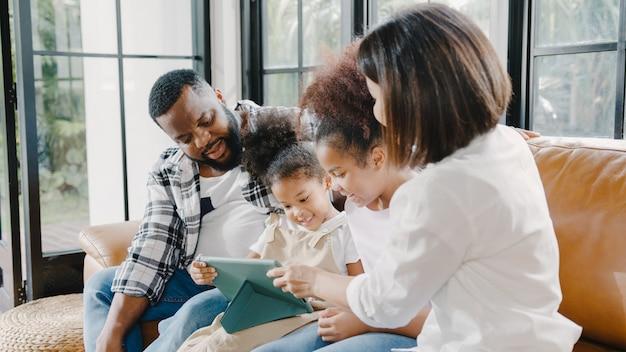 Młoda afroamerykańska rodzina i córka szczęśliwa za pomocą tabletu w domu.