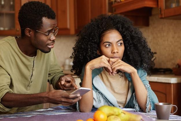 Młoda afroamerykańska rodzina walczy w kuchni z powodu romansu. mężczyzna w okularach trzymający telefon komórkowy, wskazujący palcem na ekran, próbujący wyjaśnić sobie miłosne wiadomości od nieznanej kobiety