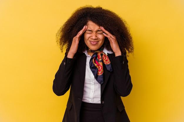 Młoda afroamerykańska stewardessa na żółto dotyka świątyń i ma ból głowy.