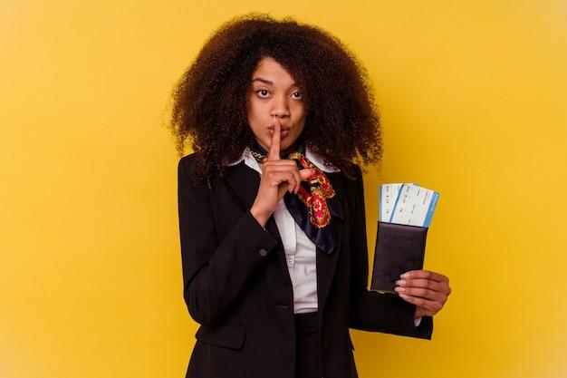 Młoda afroamerykańska stewardessa trzymająca bilety lotnicze odizolowane na żółto zachowując tajemnicę lub prosząc o ciszę.
