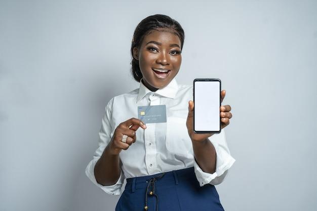 Młoda afrykanka poleca zakupy online trzymając kartę i smartfon