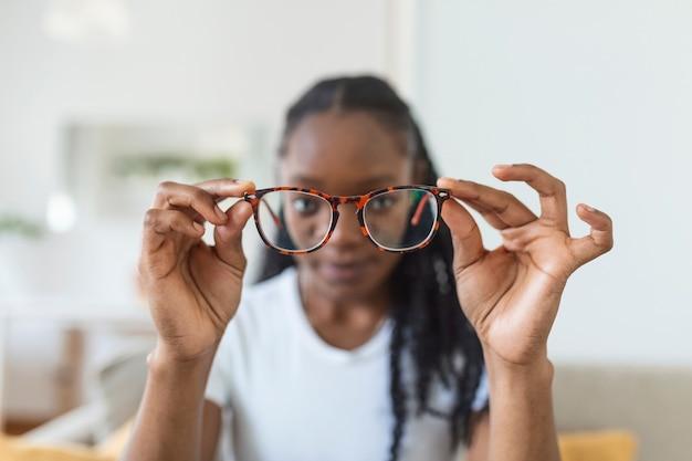 Młoda afrykanka trzyma okulary z soczewkami dioptrycznymi i patrzy przez nie, problem krótkowzroczności, korekcja wzroku