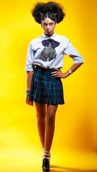 Młoda afrykańska afro kobieta nad odosobnioną kolor żółty ścianą