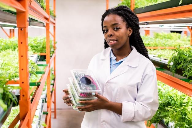 Młoda afrykańska agronomka w białym fartuchu trzyma plastikowe pojemniki ze świeżą żywnością ekologiczną i patrzy na ciebie