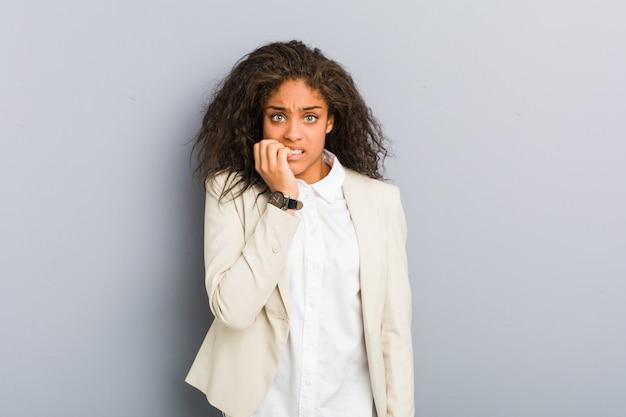 Młoda afrykańska amerykanina biznesu kobieta obgryzająca paznokcie, nerwowa i bardzo niespokojna