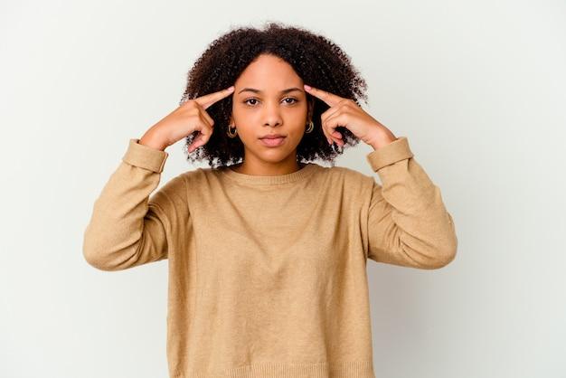 Młoda afrykańska amerykańska kobieta rasy mieszanej na białym tle koncentruje się na zadaniu, trzymając wskazujące palce wskazujące głowę.