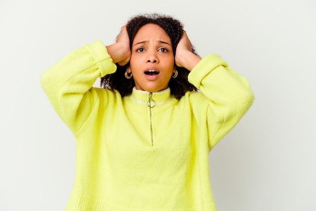 Młoda afrykańska amerykańska kobieta rasy mieszanej na białym tle krzyczy z wściekłości.