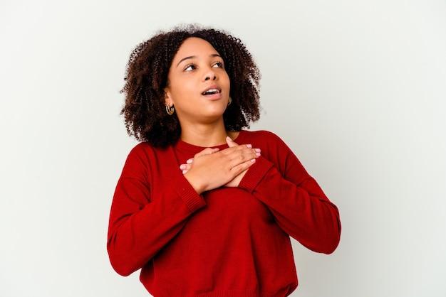 Młoda afrykańska amerykańska kobieta rasy mieszanej na białym tle ma przyjazny wyraz, naciskając dłonią na klatkę piersiową. koncepcja miłości.