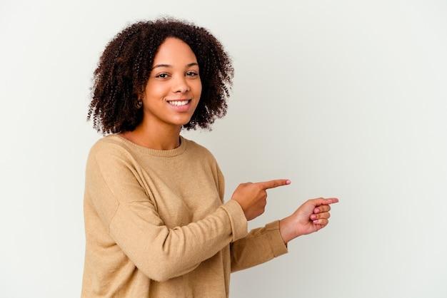 Młoda afrykańska amerykańska kobieta rasy mieszanej na białym tle podekscytowany, wskazując palcami od hotelu.