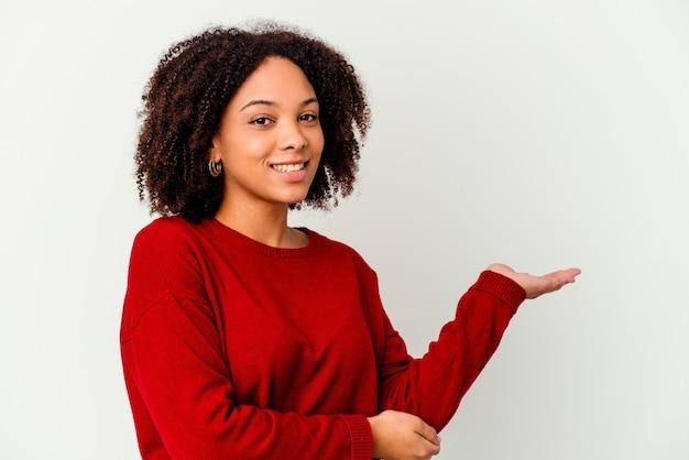 Młoda afrykańska amerykańska kobieta rasy mieszanej na białym tle pokazując miejsce na kopię na dłoni i trzymając drugą rękę na talii.